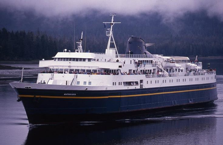 Image of the Matanuska Ferry with forest, mountain, and fog in the background.